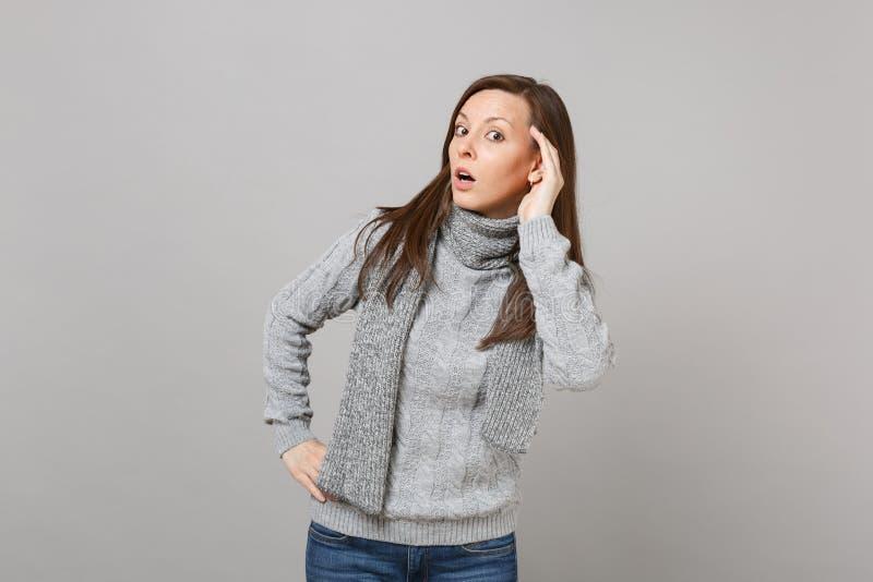 Ciekawa młoda kobieta w szarym pulowerze, szalik podsłuchuje przesłuchanie gest na popielatym tle w studiu Zdrowy zdjęcie stock