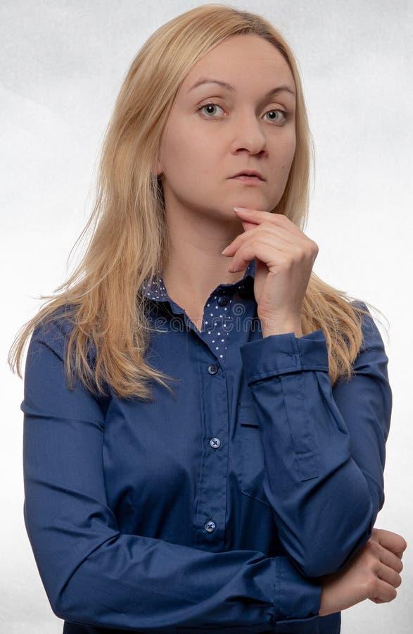 Ciekawa młoda kobieta w przypadkowy błękitny koszulowy patrzeć prosto w kamerę zdjęcia royalty free