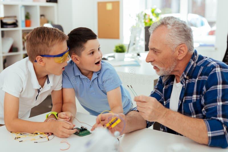 Ciekawe zdziwione chłopiec patrzeje ich nauczyciela obrazy royalty free