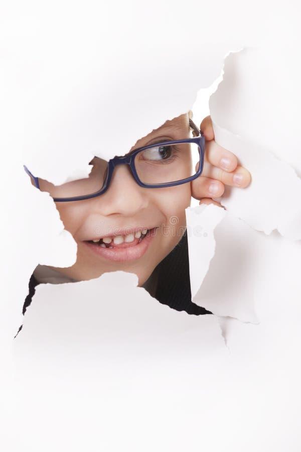Ciekawi dzieciaka spojrzenia przez dziury w papierze zdjęcie stock