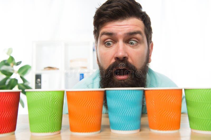 Ciekawi mężczyzn spojrzenia na kolorowych filiżankach Barwi twój dzień Różni typy kawowi napoje w cukiernianym menu ampuła obrazy stock