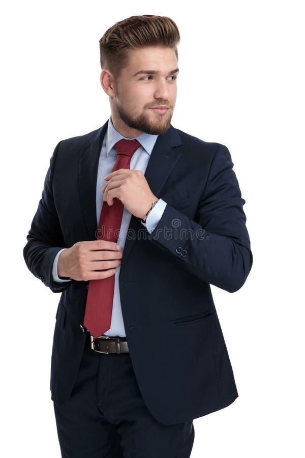 Ciekawy biznesmen załatwia jego i patrzeje nad jego ramieniem krawat obraz royalty free