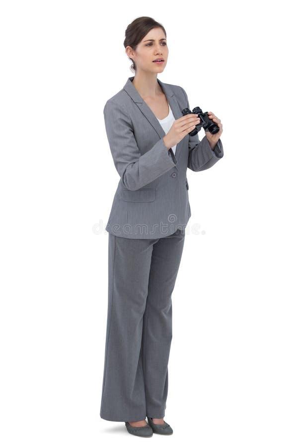 Ciekawy młody bizneswoman z lornetkami fotografia stock
