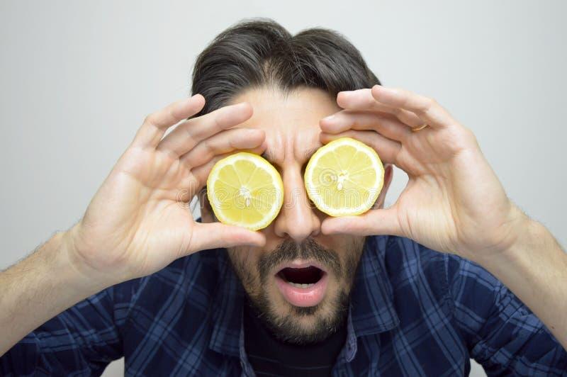 Ciekawy młody człowiek zakrywa jego ono przygląda się z cytrynami odkrywa rzecz, nowego produkt nowych/ zdjęcia stock
