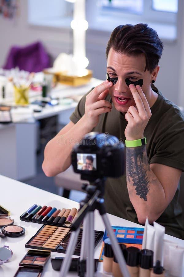 Ciekawy nadzwyczajny mężczyzny obsiadanie przy stołem otaczającym z makeup fotografia stock