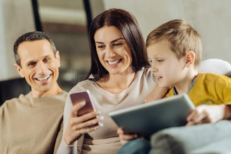 Ciekawy rodzinny zerkanie przy matka telefonem obraz royalty free