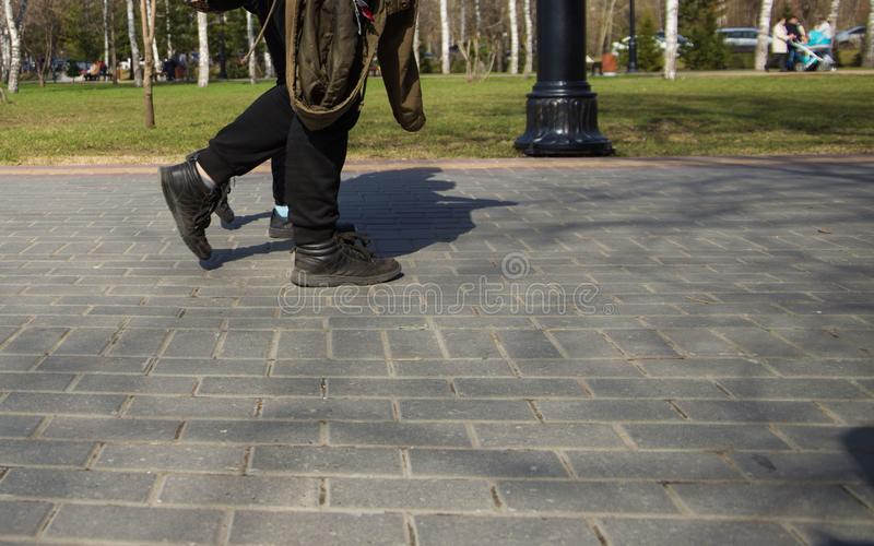 Cieki ludzie chodzi w sport?w butach zestrzelaj? ulic? na s?onecznym dniu zdjęcia royalty free