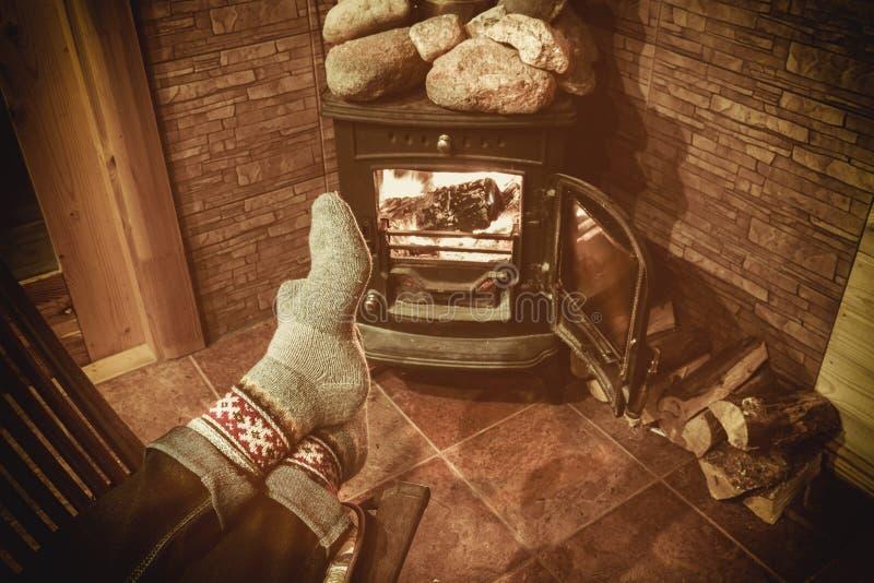 Cieki w włóczkowych skarpetach Bożenarodzeniową grabą Mężczyzna relaksuje ciepłym ogieniem z filiżanką gorący napój i rozgrzewkow obraz stock