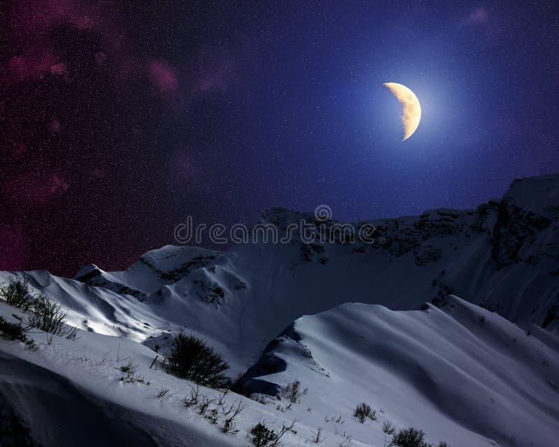 Ciel étoilé avec la lune au-dessus des montagnes couronnées de neige image libre de droits