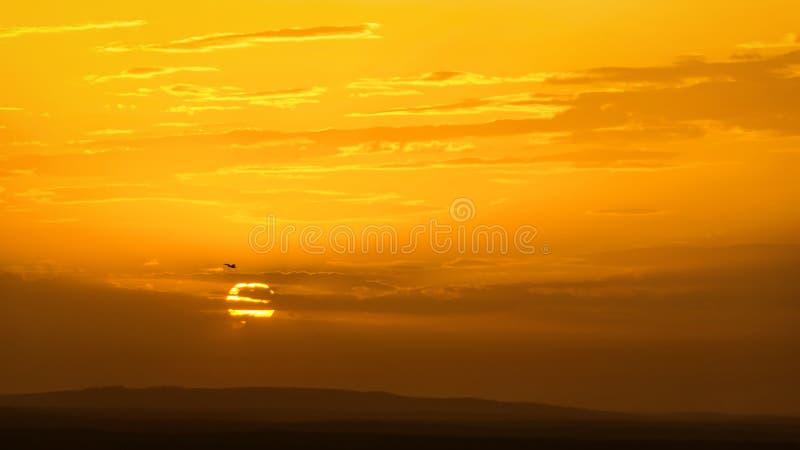 Ciel avec l'avion au coucher du soleil image stock