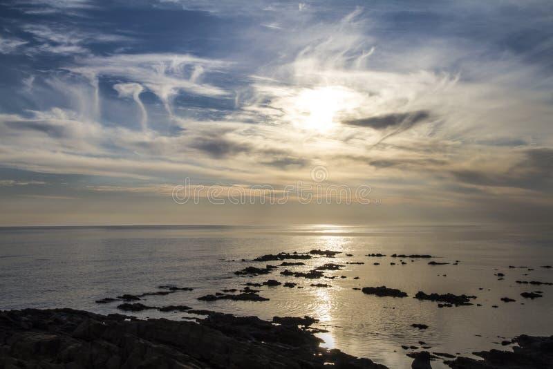 Ciel bleu à l'aube couverte par des formations étranges de nuage sur une mer plate de roches noires qui se tiennent dans la réfle images stock
