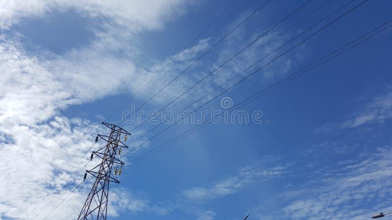 Ciel bleu au-dessus de la ville et de la ligne à haute tension dans l'intervalle images libres de droits
