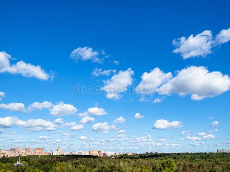 Ciel bleu avec beaucoup de nuages de blanc au-dessus de bois et de ville image stock