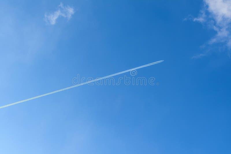Ciel bleu avec la traînée de condensation photographie stock