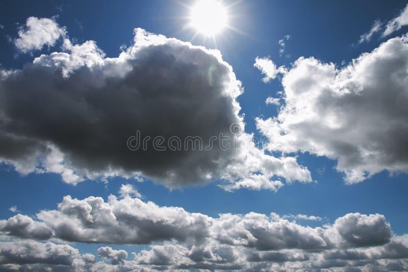 Ciel bleu avec les nuages et le soleil pelucheux blancs avec des rayons photos libres de droits