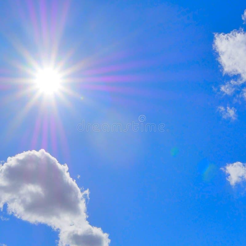 Ciel bleu avec les nuages et les rayons de la lumière blancs gonflés du soleil photos stock