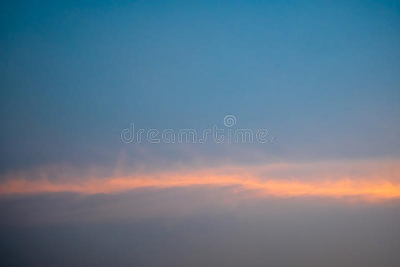 Ciel bleu avec les nuages pelucheux blancs, rayons de lumière oranges horizontalement pendant le coucher du soleil photo stock