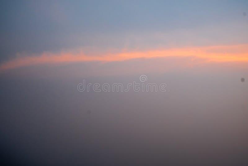 Ciel bleu avec les nuages pelucheux blancs, rayons de lumière oranges horizontalement pendant le coucher du soleil photographie stock libre de droits