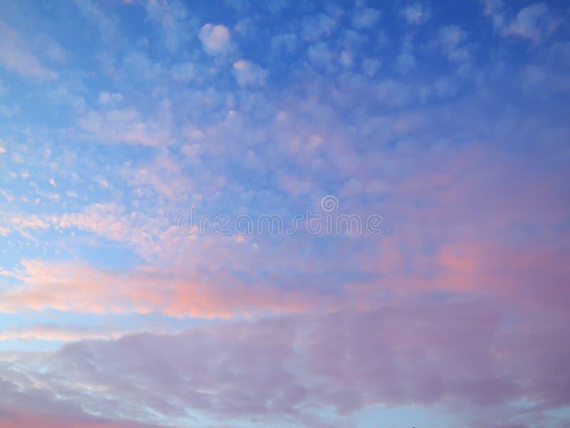 Ciel bleu avec les nuages roses et pourpres photos stock