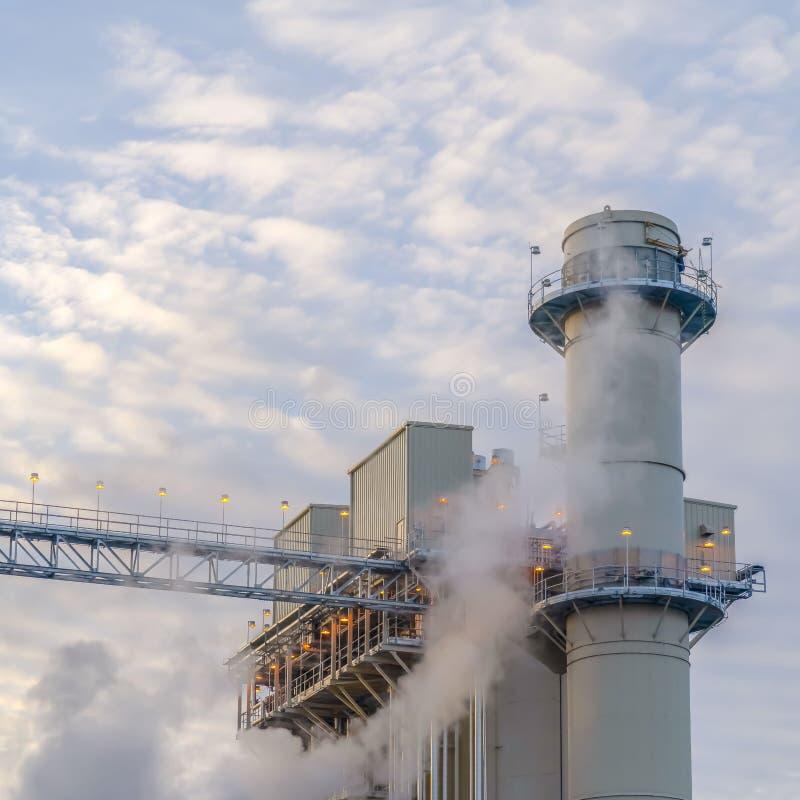 Ciel bleu de place avec les nuages gonflés derrière la tour et les bâtiments d'une centrale photographie stock libre de droits