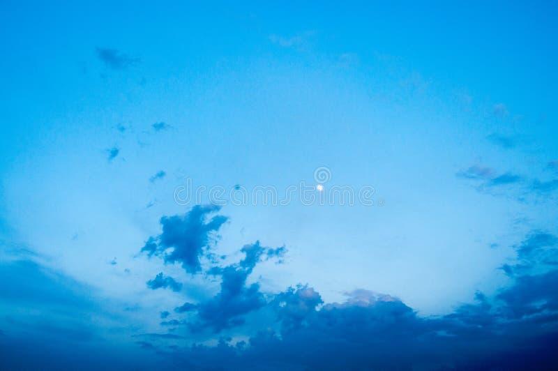 Ciel bleu-fonc? de soir?e La jeune lune est haute Beaux nuages photo libre de droits