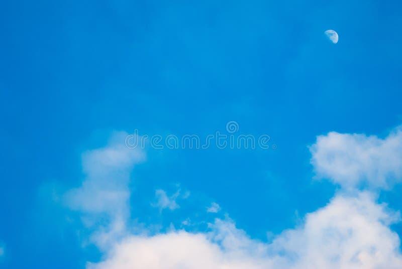 Ciel bleu lumineux avec la lune et les nuages, photos stock