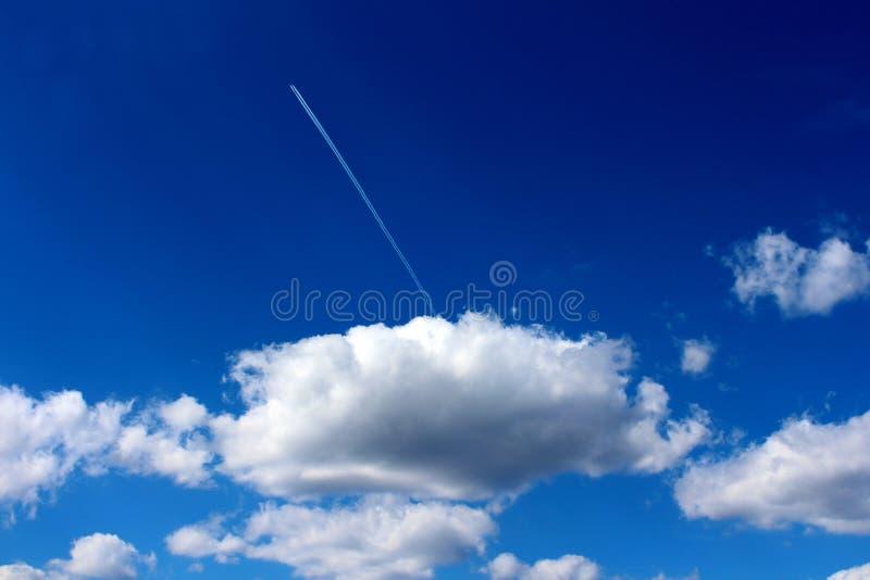 Ciel bleu nuageux avec le grand nuage gris-foncé blanc et deux les traînées blanches d'avion allant à partir de lui ressemblant a photographie stock