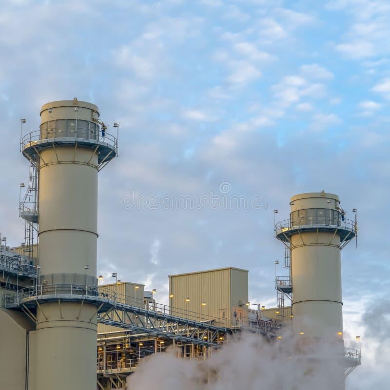 Ciel bleu nuageux de place vu derrière les tours et les bâtiments d'une centrale photos libres de droits