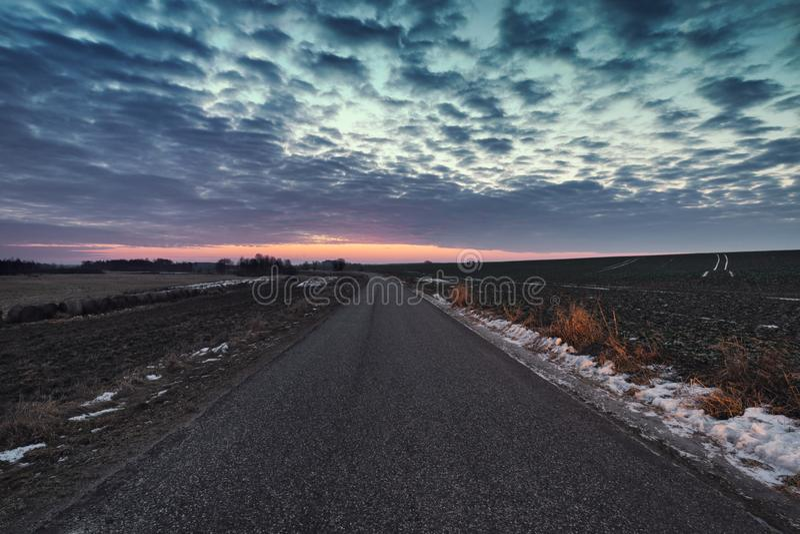 Ciel crépusculaire au-dessus d'Asphalt Road vide à l'hiver image libre de droits
