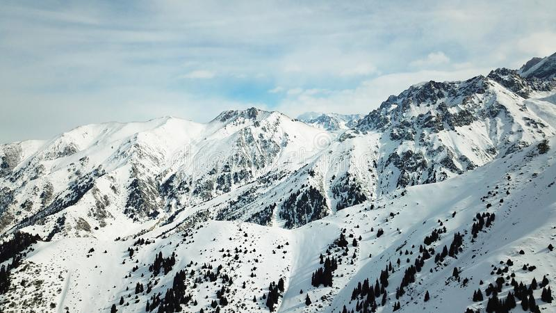 Ciel dans les nuages donnant sur les crêtes couronnées de neige des montagnes photos libres de droits
