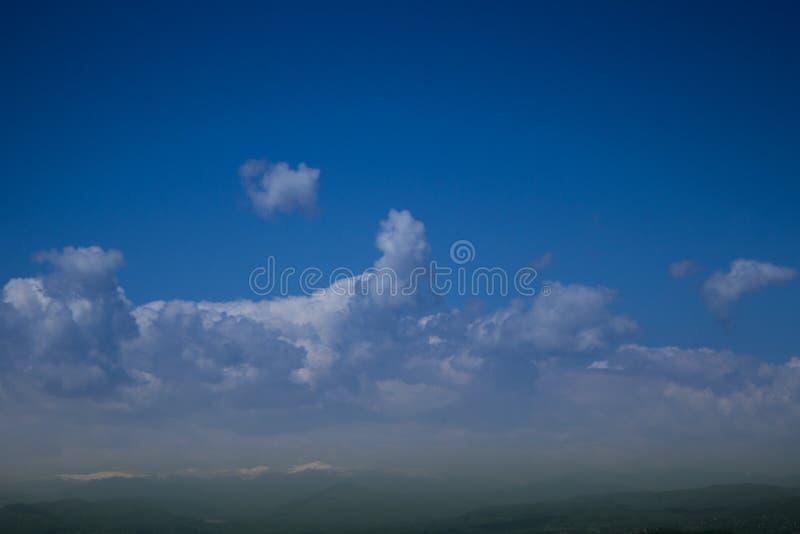 Ciel de bleu marine avec des nuages au-dessus des dessus de montagne photos stock