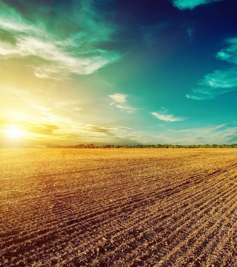 Ciel de coucher du soleil au-dessus de champ labouré image stock