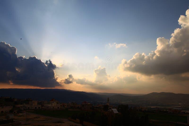 Ciel de coucher du soleil avec des nuages au-dessus de ville arabe images stock