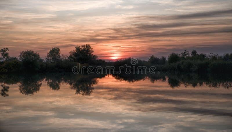 Ciel de coucher de soleil dramatique avec nuages colorés sur le lac photo stock