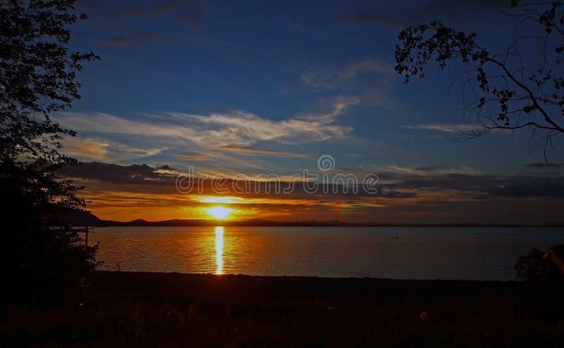 Ciel de ternissure de coucher du soleil au-dessus du lac avec les nuages colorés, heure d'or images libres de droits