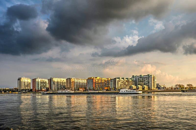 Ciel dramatique au-dessus de lotissement au bord de l'eau moderne photos stock
