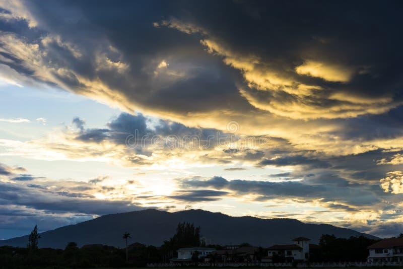 Ciel dramatique avec les nuages foncés au-dessus de la montagne au coucher du soleil photographie stock