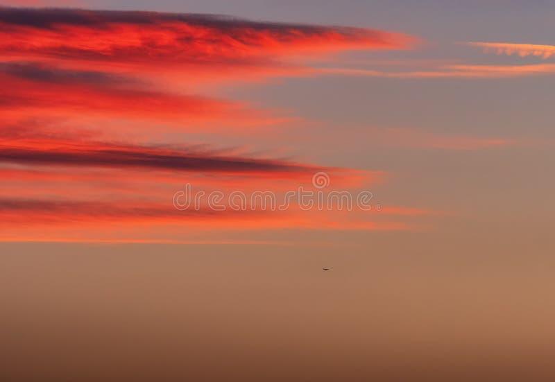 Ciel dramatique de coucher du soleil avec des nuages et un petit avion photo libre de droits