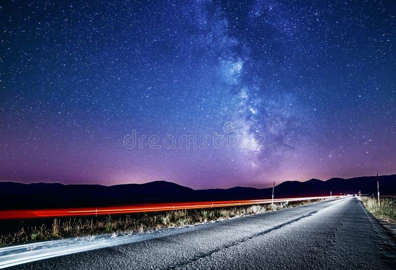 Ciel nocturne avec la manière laiteuse et les étoiles Route de nuit illuminée en la voiture photographie stock libre de droits