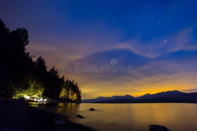 Ciel nocturne orange et bleu avec camper de tentes photos stock