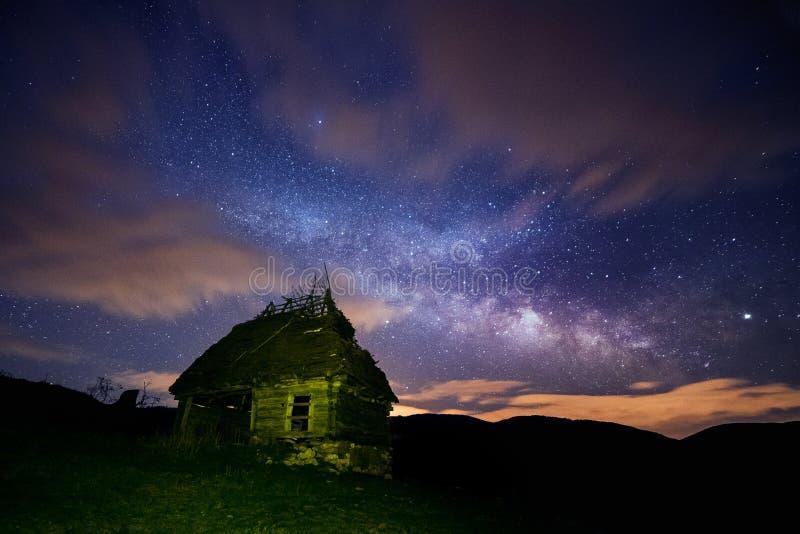 Ciel nocturne plein des étoiles avec quelques nuages et la galaxie de manière laiteuse et une vieille maison rustique de grange d photographie stock