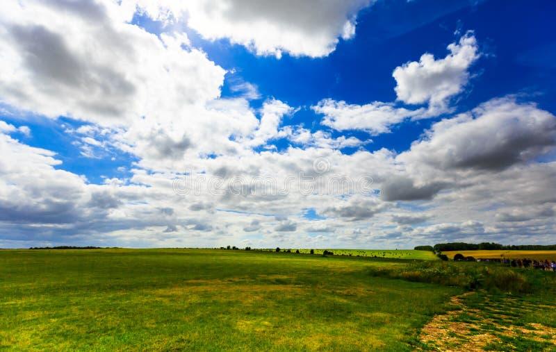 Ciel nuageux bleu réaliste avec le soleil lumineux au-dessus du champ vert de pré image libre de droits