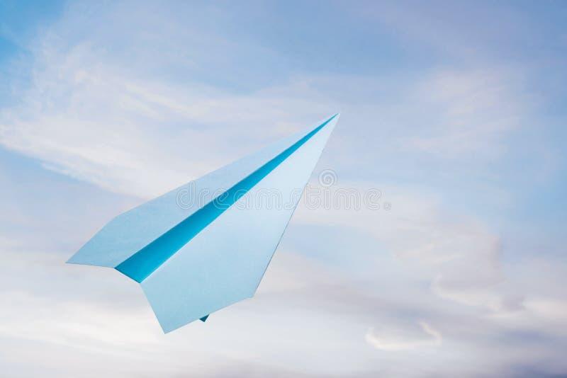 Ciel nuageux d'agains d'avion de papier bleu images stock