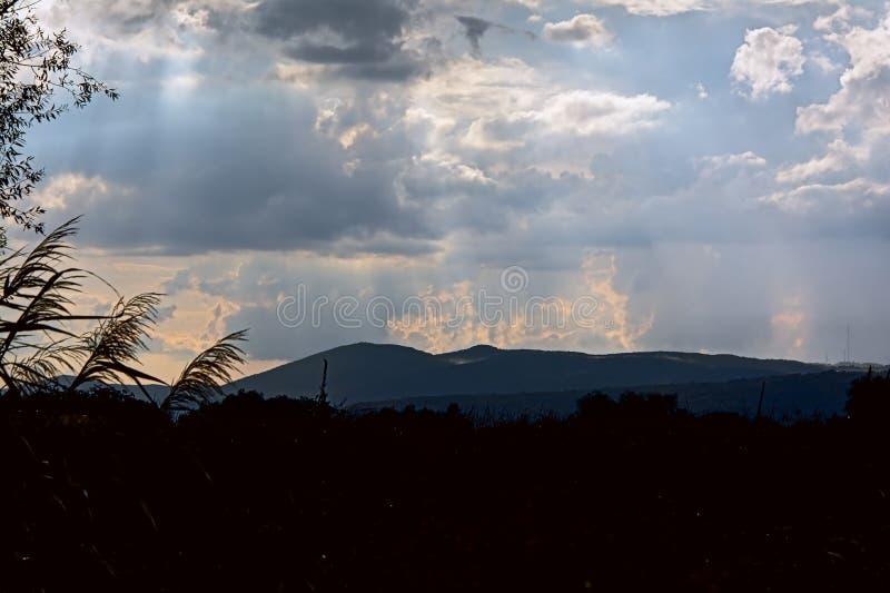 Ciel nuageux dans la lumière de soirée au-dessus de la silhouette des montagnes roumaines images stock