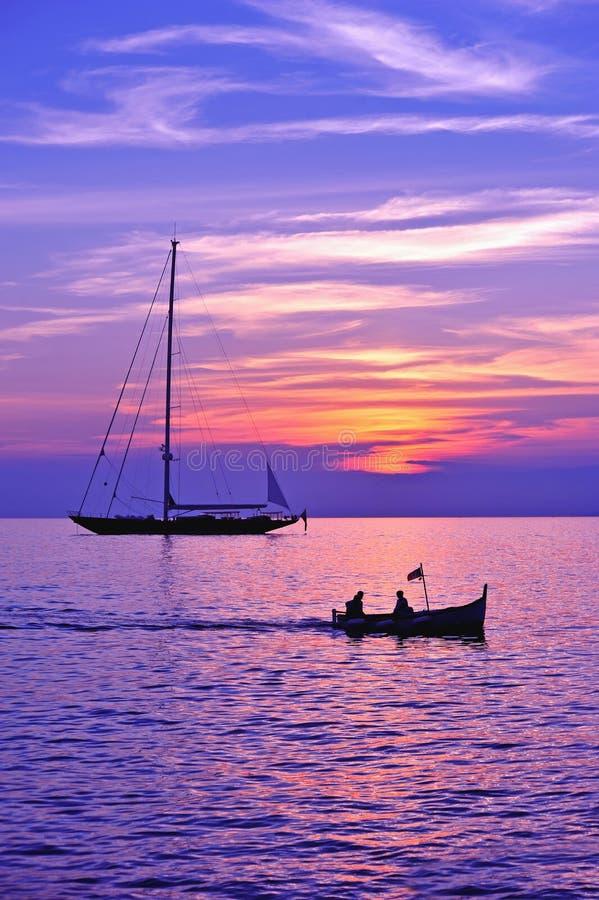 Ciel pourpre avec la silhouette de bateau et de bateau de navigation photographie stock libre de droits