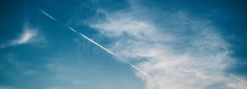 Ciel profond stupéfiant de bleu de vue cloudly et traînée blanche des moteurs de l'avion photos libres de droits