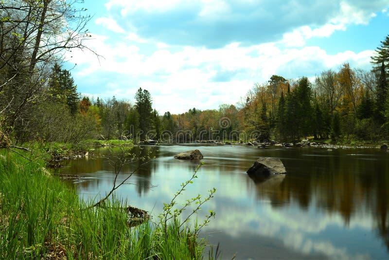 Ciel réfléchi dans le calme de rivière photos libres de droits