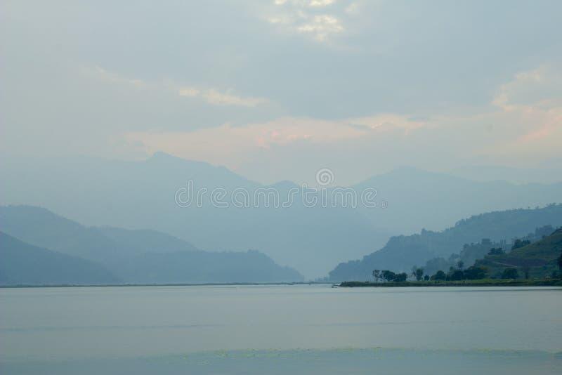 Ciel tendre rose bleu de coucher du soleil dans une vallée verte de montagne au-dessus du lac le soir Silhouettes de montagnes photo libre de droits