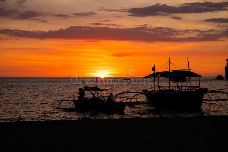 Ciel vibrant de coucher du soleil et paysage de mer avec le bateau en bois Paysage marin calme sur l'île tropicale Calibre orange image libre de droits
