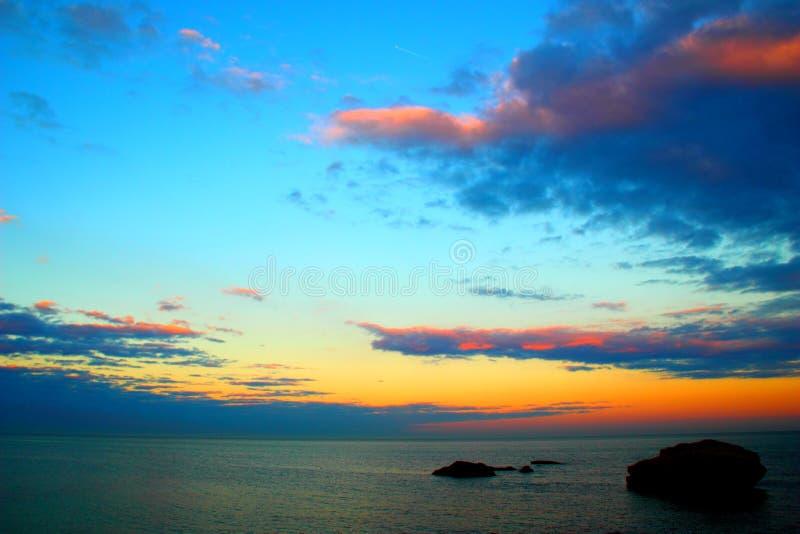 Ciel vif au-dessus de la mer avec des roches photos stock